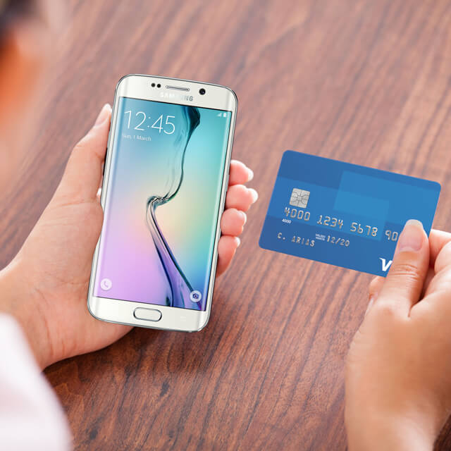 A closeup of a person holding their Samsung phone and Visa card.
